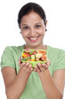 Smiling young woman holding fruit salad