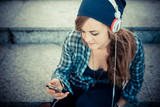 beautiful young blonde hipster woman listening music