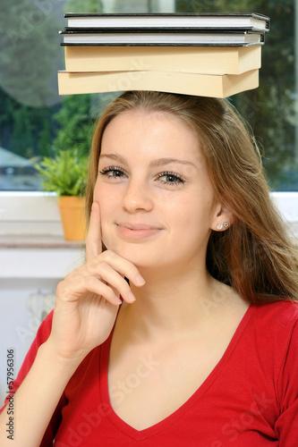 Kreative Schülerin mit Büchern auf Kopf