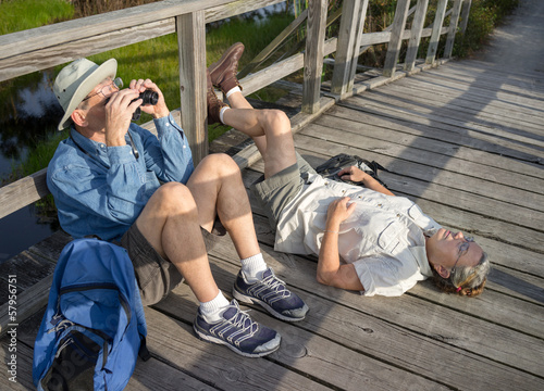 Senior couple birdwatching and relaxing during hike
