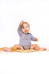 Baby spielt mit Nudeln