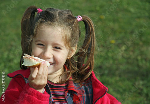 young girl while eating the sandwich