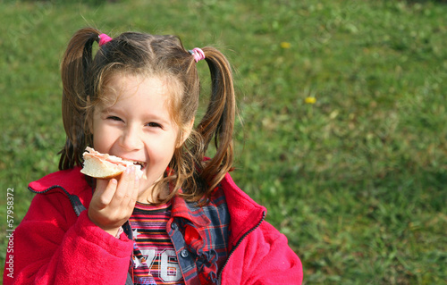 young girl while eating the sandwich, smiling