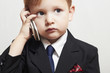 child in business suit with cell phone.fashionable little boy