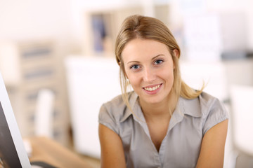 Portrait of beautiful office-worker sitting at desk