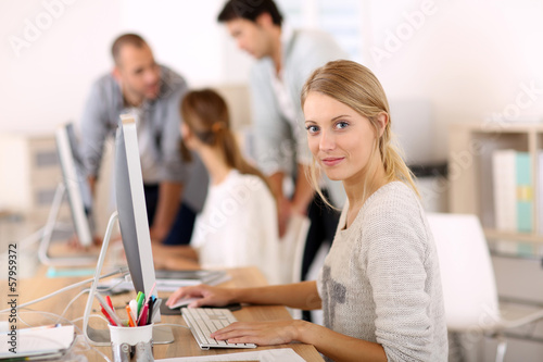 canvas print picture Young girl in office working on desktop computer