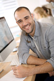 Fototapety Cheerful guy sitting in front of desktop computer