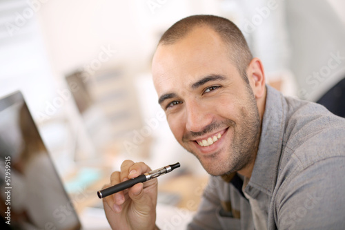 Portrait of cheerful guy smoking with e-cigarette