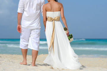 wedding couple walking away on the beach