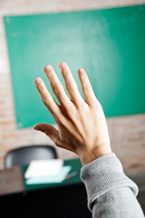 Student's Hand Against Greenboard In Classroom