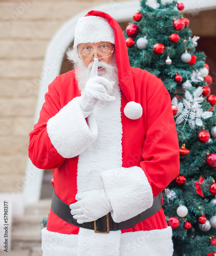 Santa Claus With Finger On Lips Against Christmas Tree