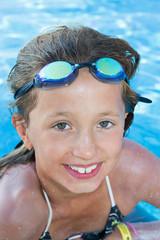 Mädchenmit Schwimmbrille am Beckenrand