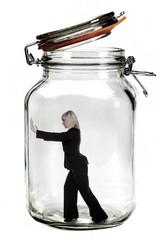 Businesswoman trapped inside a transparent glass jar.