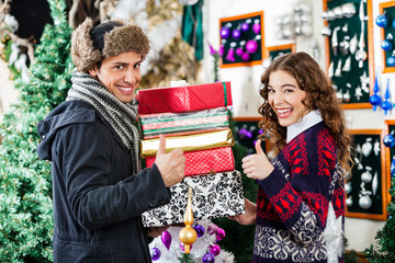 Couple Gesturing Thumbs Up While Holding Christmas Presents