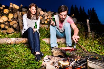 Alpen - Paar beim Lagerfeuer in den Bergen
