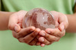 Hands holding glass globe