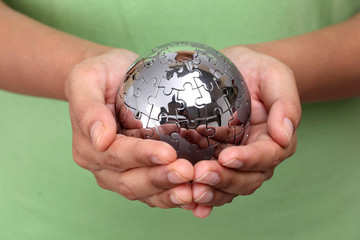 Hand holding metal puzzle globe