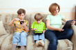 Two brothers and mother sit on divan with electronic gadgets