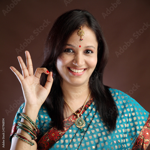 Portrait of young traditional woman making OK sign