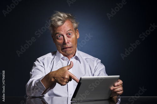 Man pointing to his laptop in horror and disbelief
