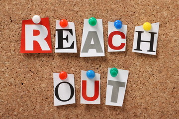 The phrase Reach Out on a cork notice board