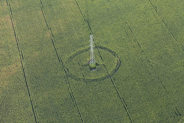 aerial view of electric post on harvest field