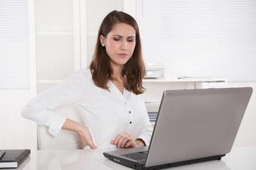 Junge Frau krank mit Rückenbeschwerden im Büro
