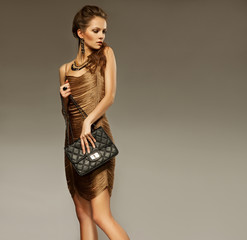 Portrait of beautiful young woman with a leather bag. Fashion ph
