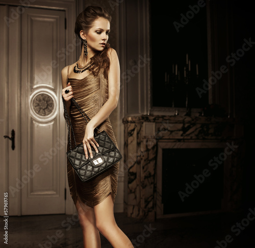 Elegant beautiful woman holding a bag in a luxury room