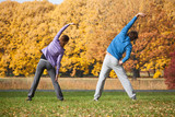 Fototapety Couple exercising in park in fall