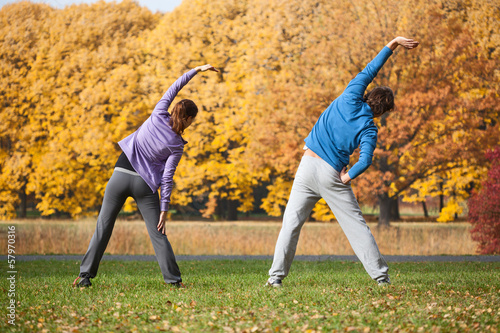 Couple exercising in park in fall
