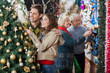 Couple Looking At Christmas Tree While Parents Shopping In Store