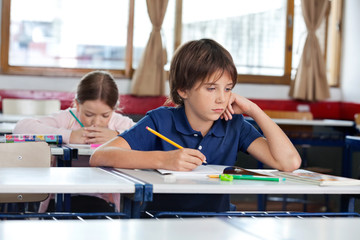 Boy Looking Away While Writing In Book