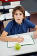 Shocked Schoolboy With Cheat Sheet Sitting At Desk