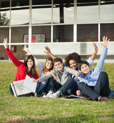 College Students With Hands Raised Sitting At Campus