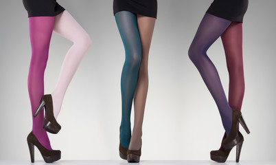 collection of colorful stockings on sexy woman legs on grey