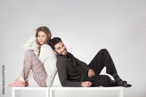 Happy couple in pyjama posing in the studio