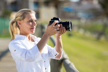middle aged woman taking photos outdoors
