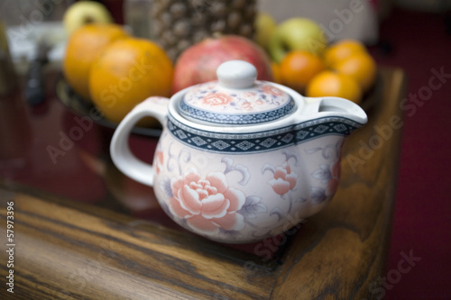 Chinese teapot and fruits on coffee table.
