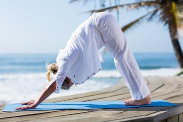mid age woman yoga exercise on beach