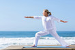 mature woman yoga exercise on beach