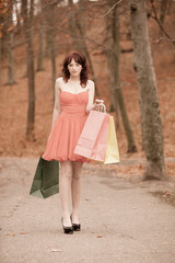 Elegant shopper woman walking in park after shopping