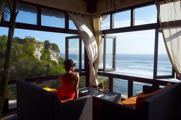 young woman looking at sea at a cafe