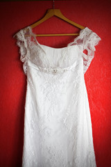 White wedding dress on the red wall. Close-up