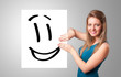 Young woman holding smiley face drawing