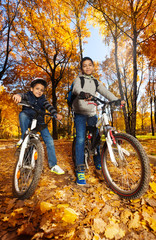 Boys rides bicycles in the park