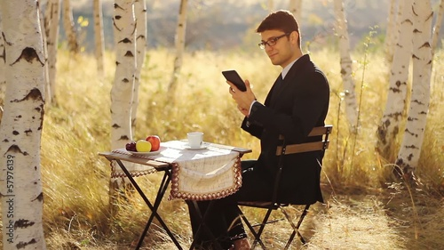 Businessman Using tablet outdoors breakfast in nature concept