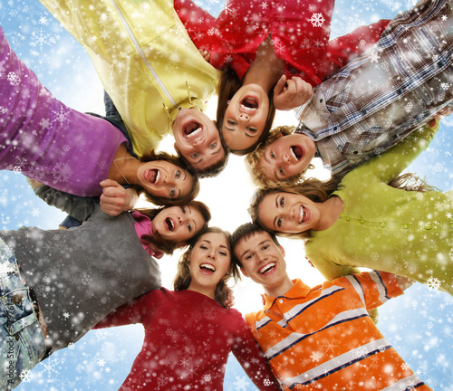 Group of smiling happy teenagers over Christmas background