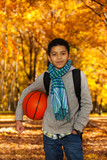 Boy holding basketball ball outside