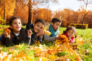 Group of kids lay in autumn leaves